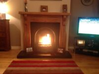 Wooden fireplace with black cast iron insert and black tiled hearth. Good condition