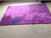 100% wool floor rug. Shades of dark pink and purple.