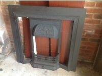 Inset black decorative cast iron fire surround with tile bars and fire back