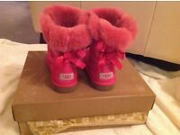 Bright pink bailey button ugg boots with bow design