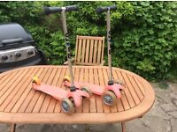 A pair of pink Mini Micro T-bar scooters