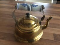 Brass kettle with blue and white ceramic handle.