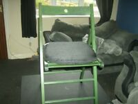green wooden fold up chair with seat pad