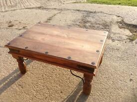 Wooden coffee table with cast iron detailing.