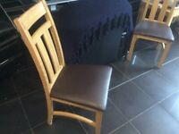 Solid oak chairs in great condition with brown leather seat.