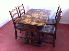 Solid wooden dining table with 4 matching chairs.
