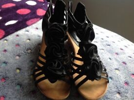 Black heeled sandals with rose detailing and zip back