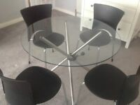 Glass dining table and four black chairs, with silver coloured legs.