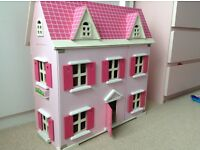 Large wooden dolls house with lots of furniture and five dolls
