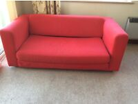 Red 2 seater sofa bed.