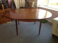 GPlan teak dining table. Circular and extendable to oval. Seats 8-10 extended. As new.