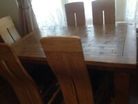 Beautiful long oak extendable dining table and 6 oak/black leather chairs.