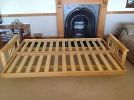 Futon/sofa bed with light wood frame.