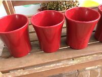 Three red ceramic pots for flowers and plants