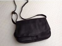 Black leather handbag with numerous sections, including zipped sections