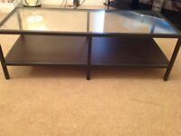Glass top coffee table with black shelf