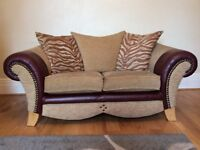 2 x two seater sofas, both identical with brown leather arms and studs along with material cushions.