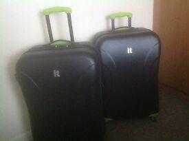 Two black and lime green IT medium suitcases