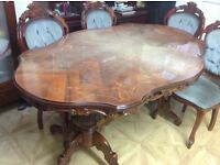 DINING table with 6 chairs, oval curved shape.