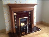 Wooden fire surround with tiled hearth and inset.