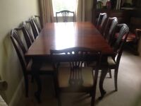 Solid mahogany table with chairs, extends to 10-12 persons. Has 2 extra sections and turn handle.