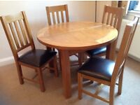 Round Oak extending dining table with four brown leather chairs