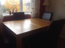 Oak dining table with four chairs.