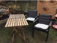 2 foldable tables and 2 black wooden chairs with cushions