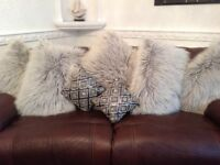 Grey and cream goat skin rug and grey fluffy cushions