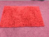 Red fluffy rug in excellent condition