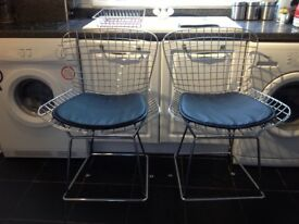 Designer bar stools in heavy stainless steel and seat pads in the style of knoll bertoia