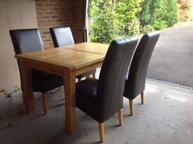 Solid oak extending dining table set with four brown faux leather chairs