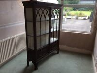 Mahgony display cabinet with glass display doors with enclosed shelf at the bottom.