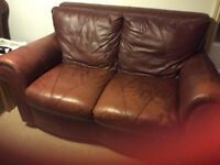 Two matching brown leather sofas