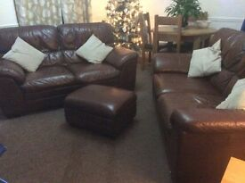 Two chocolate brown leather sofas with matching puffy