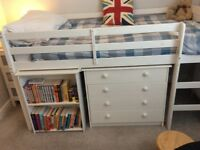 Mid sleeper child bed set including chest of drawers and pull out desk with shelves.