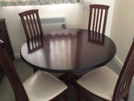 Dark wood round extendable dining table and 4 high back chairs