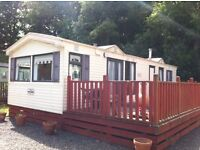 Willerby Cottage 2 bedroom 35x12 static caravan for sale with a large wooden deck on a luxury pitch