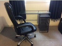 Steel desk with glass top, separate drawers and black leather swivel chair.