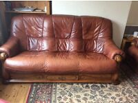 2 brown three seater leather sofas in a wooden frame. Wooden frame has a draw with a brass handle
