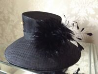 Large brimmed black hat with feathers.