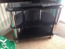 Two dark glass television stands. Metal legs and glass shelves