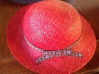Ladies light red summer straw hat with navy/red ribbon detail around.