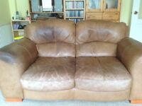 Two very comfy leather two seater sofas .