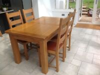 Solid Solid oak dining table, four oak chairs with leather seats excellent condition.