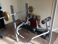 York fitness bench, with accessories and assorted weights.