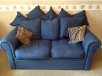 3 seater sofa which turns into a double bed. Dark blue fabric upholstery.