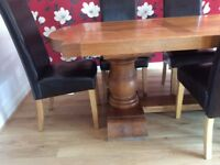 Solid oak dining table and 8 high back leather chairs.