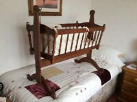 Wooden rocking cot complete with virtually new mattress, bumper with cover and 2 fitted sheets.