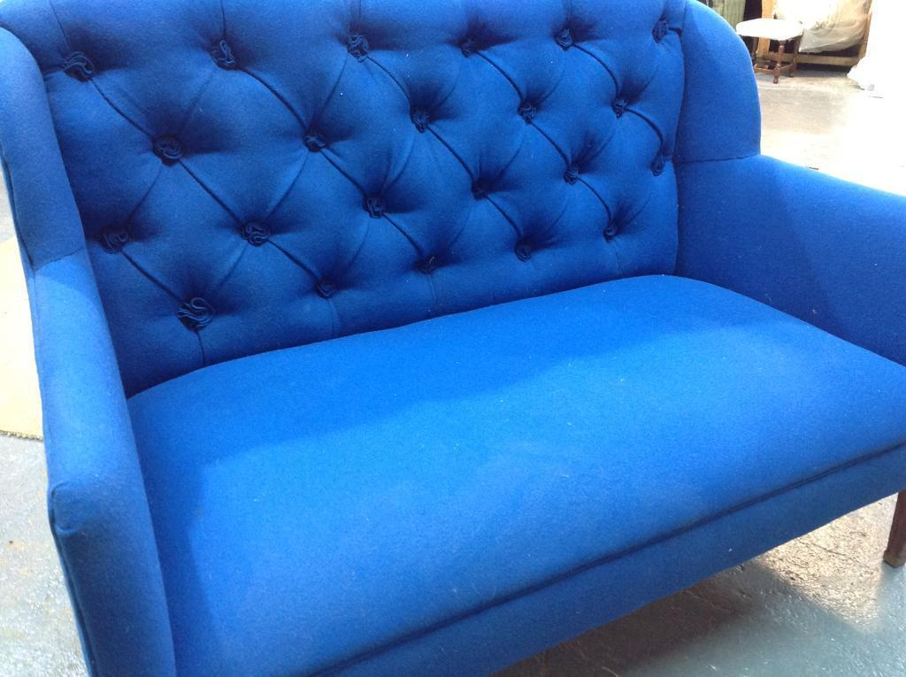 Small blue buttoned sofa.